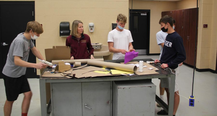 Brooke Hart helps sophomores Tanner Boyd and Baker Calvert put the final touches on their homemade shoes in manufacturing class.